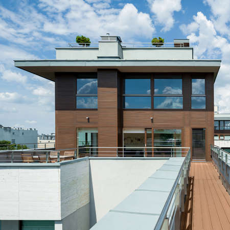 Exterior view of modern apartment building with big terrace