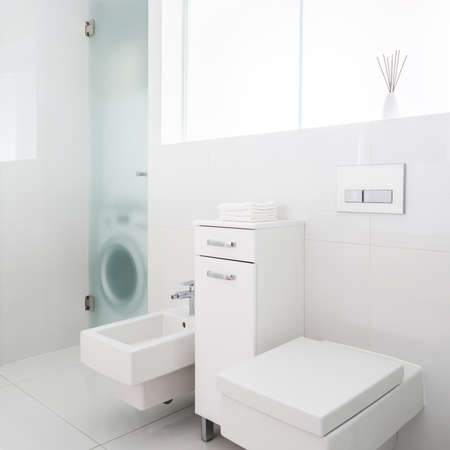 Simple and functional bathroom with window, white tiles, modern square toilet and bidet and washing machine behind frosted glass doors