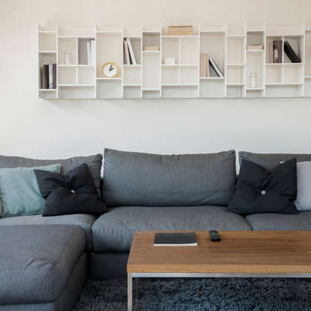 Modern white shelf with books and decorations above comfortable, gray corner sofa