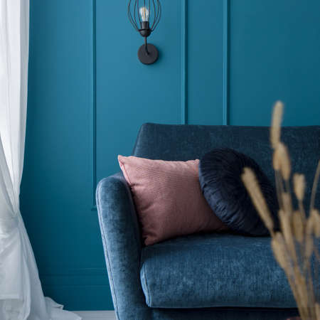 Close-up on nice blue sofa with decorative pillows in room with teal blue wall with molding, white curtains and black lamp