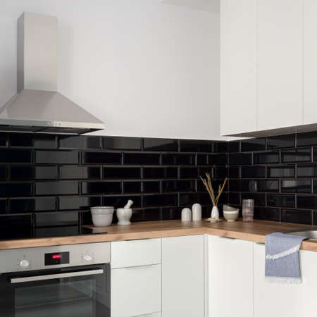 Small and stylish kitchen with black brick tiles, white furniture, silver oven and kitchen hood and wooden countertops
