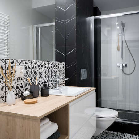 Elegant and stylish designed, small bathroom with decorative wall tiles, wooden countertop with white washbasin, big mirror and shower behind glass sliding doors