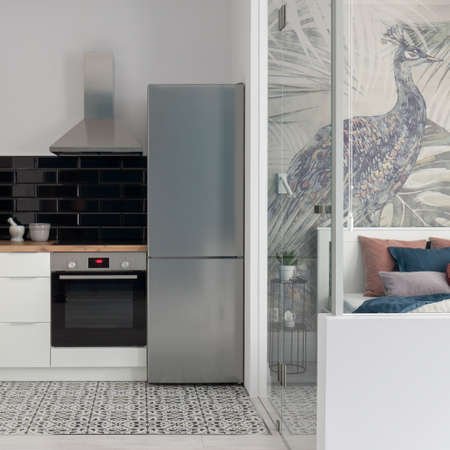 Nice and small kitchen next to bedroom with elegant wallpaper and glass doors Banque d'images