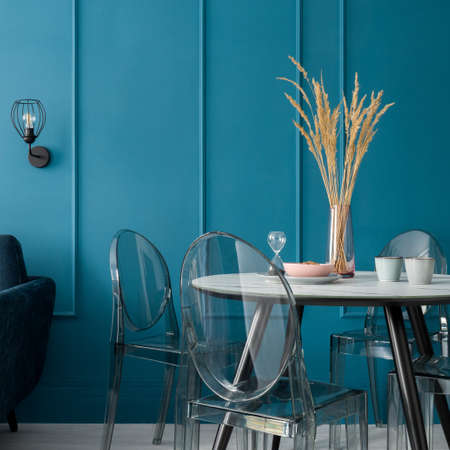 New dining table with decorations, marble style countertop with modern, four transparent chairs in elegant room with teal blue wall with molding Banque d'images