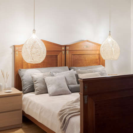 Fancy, wooden and old-fashioned style bed for two in simple bedroom with wooden bedside table and two pendant rattan lamps