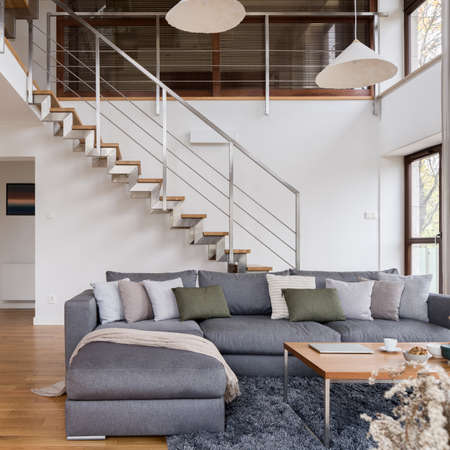 Big, comfortable corner sofa in spacious living room with modern stairs in two-storey loft apartment