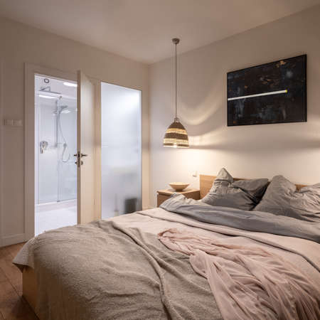 Comfortable and spacious master bedroom with big, double bed and bathroom behind frosted glass wall
