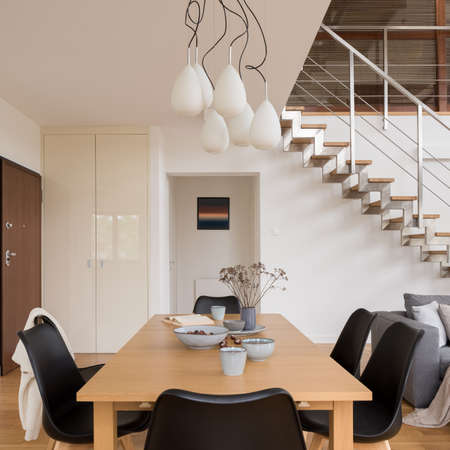 Family, wooden dining table with six black chairs in spacious, two-floor apartment with modern stairs