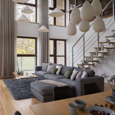 Stylish two-floor loft apartment with big windows, spacious living room with comfortable, gray corner sofa and stairs Banque d'images