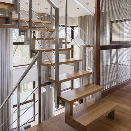 Modern staircase in storied apartment with wooden steps and silver railing Banque d'images
