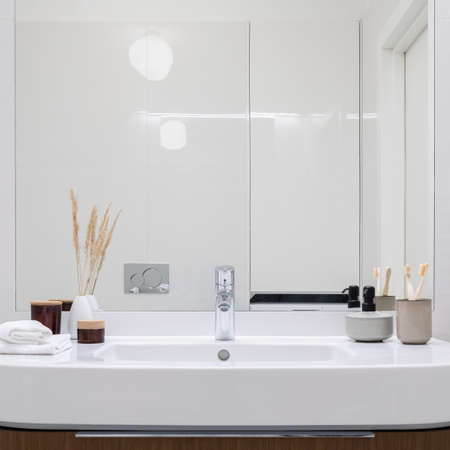 Close-up on big bathroom washbasin with silver tap, many decorations and mirror wall