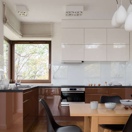 Modern kitchen with white and brown furniture, big window and with wooden dining table with black chairs Banque d'images