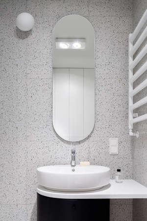 Modern bathroom with oval mirror, stylish washbasin and decorative terrazzo style wall tiles