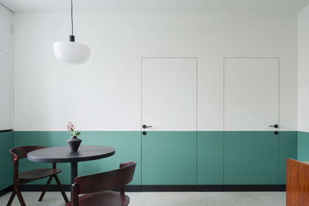 Modern dining room with dark table and chairs, simple ceiling lamp and decorative wall and doors half white and green Banque d'images