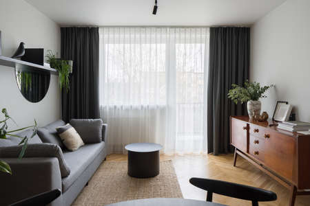 Retro style, wooden sideboard in simple and modern designed living room with big window