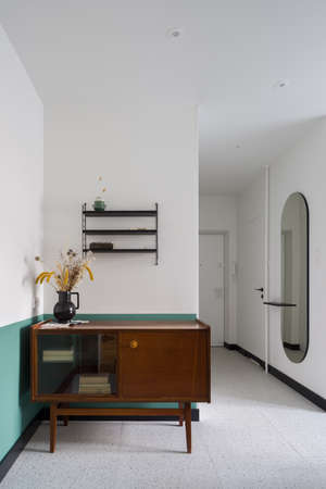 Vintage, wooden sideboard with decorations and books in modern apartment with stylish terrazzo on the floor