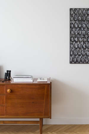 Close-up on wooden vintage sideboard and modern art on the wall