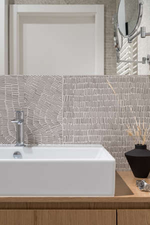 Close-up on classic white washbasin in wooden cabinet with decorations in modern bathroom with stylish and patterned wall tiles Banque d'images