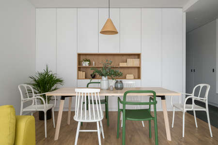 Simple and nice dining room with long wooden table, different and stylish, white and green chairs