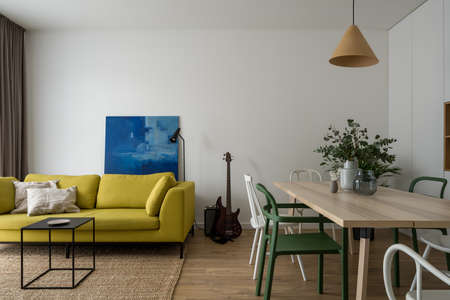Apartment with modern and stylish living room with comfortable, yellow sofa and nice black coffee table and dining area with wooden table and different chairs