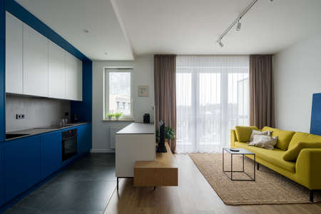 Contemporary apartment interior with modern designed kitchen with blue cupboards open to stylish living room with yellow couch Banque d'images