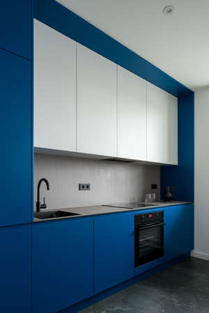 Amazing, modern design in kitchen with stylish blue walls and cupboards, gray countertop and backsplash and white upper cabinets