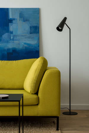 Modern, yellow couch and simple, black lamp in bright living room with white walls and art Banque d'images