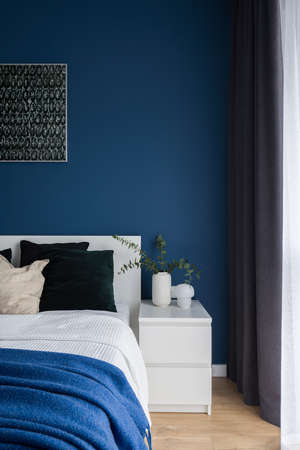 Simple, white bedside table next to comfortable bed in bedroom with dark blue wall