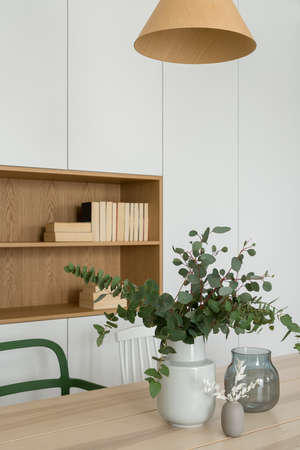 Stylish decorations, vase and plants on wooden dining table in room with white cabinets and wooden shelf