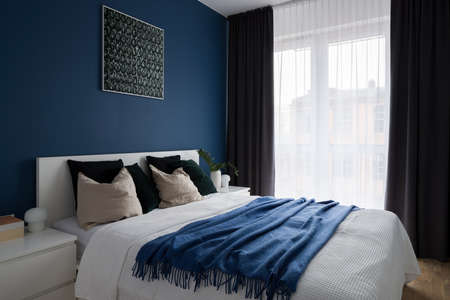 Comfortable bedroom with double bed, big window and modern blue wall
