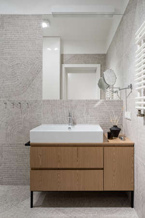 Stylish and modern bathroom with decorative and patterned floor and wall tiles, elegant white washbasin with wooden cabinet and big mirror