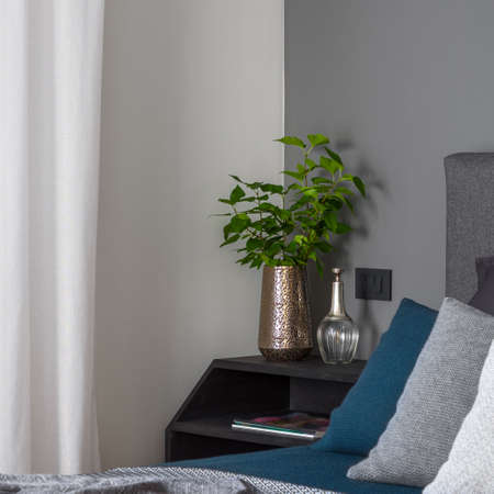 Close-up on stylish golden vase with green plant and decorations on simple, black nightstand next to cozy bed in bright bedroom