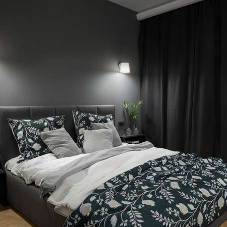 Big and comfortable bed in stylish and dark bedroom with gray walls, curtains and nice lighting