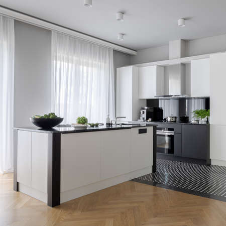 Elegant and spacious kitchen with black and white furniture, big window behind curtains and functional kitchen island