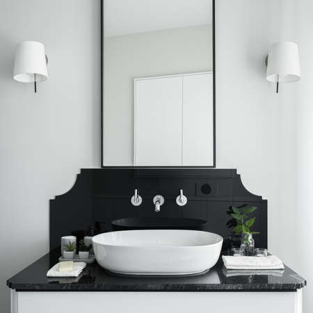Close-up on stylish bathroom washbasin on white cabinet with black countertop and big mirror