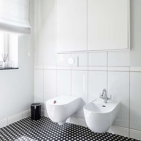 Close-up on stylish bidet and toilet in modern bathroom with black and white mosaic tiles on the floor