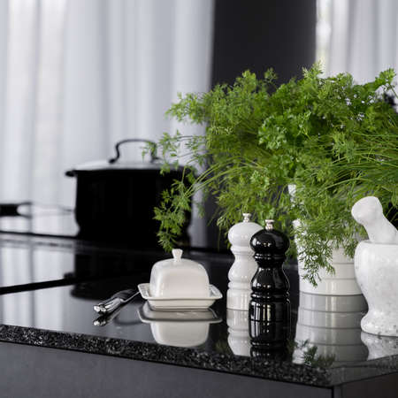 Close-up on black, granite kitchen countertop with decorative, white butter dish, stylish black and white salt and pepper shakers, mortar and fresh, green herbs in flower pots