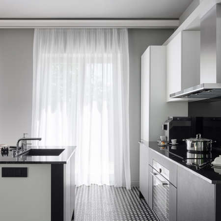 Modern black and white kitchen with big windows behind white curtains and with black and white kitchen island with sink and black and white furniture with black countertops Archivio Fotografico
