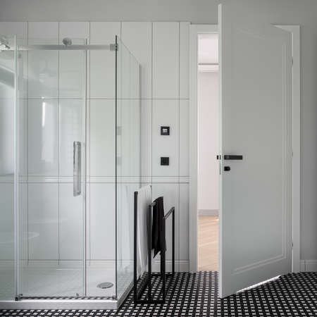 Modern bathroom in black and white with stylish mosaic floor tiles and shower