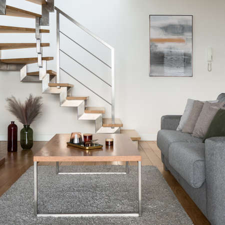 Close-up on simple, wooden coffee table with decorations in living room comfortable sofa and with stairs to second floor