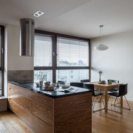 Stylish and bright kitchen with big window, wooden floor, nice kitchen island with black countertop and with wooden dining table with black chairs under pendant lamp Banque d'images
