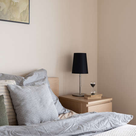 Close-up on stylish black lamp on simple, wooden bedside table with decorations next to comfortable bed with gray bedclothes