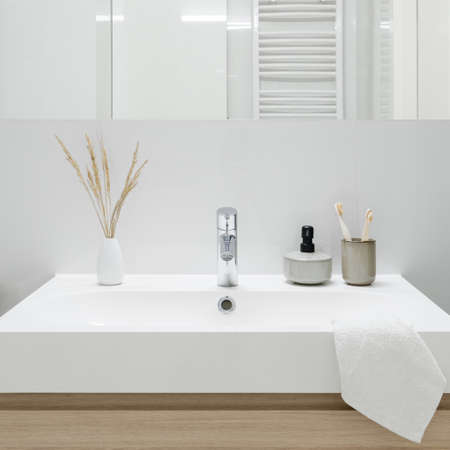 Close-up on classic and white bathroom washbasin with decorations under mirror