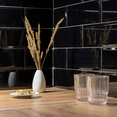 Close-up on decorative vase with dried grass, glasses and plate on wooden countertop in kitchen with black wall tiles