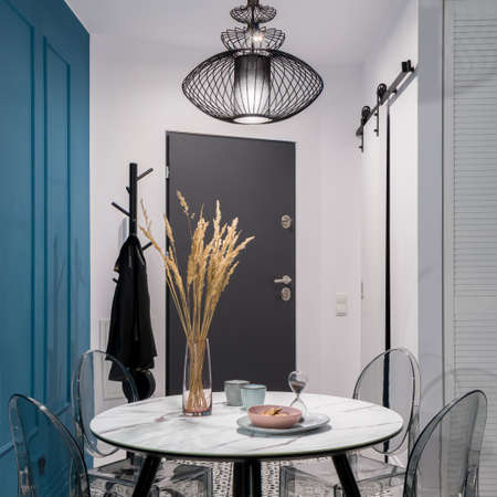 Small studio apartment with stylish dining table with transparent chairs under black, pendant lamp open to white entryway with dark doors and black clothes hanger