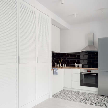 Small and stylish kitchen in black and white with big white wardrobe in bright studio apartment