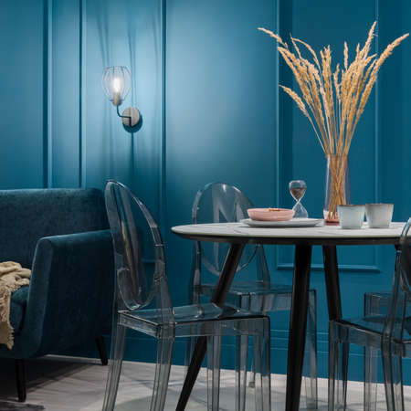Modern dining table with stylish plastic chairs in nice living room with teal blue walls with decorative molding and lighting