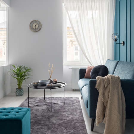 Charming and small living room with blue sofa, square ottoman and simple coffee table on fluffy carpet Banque d'images