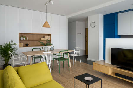 Simple and modern dining table with colorful and different chairs in stylish living room with tv open to kitchen area Banque d'images