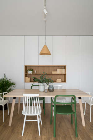 Modern designed dining room with simple, wooden table and various and colorful chairs Banque d'images
